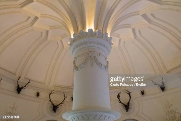 Low Angle View Of Column By Hunting Trophies On Wall