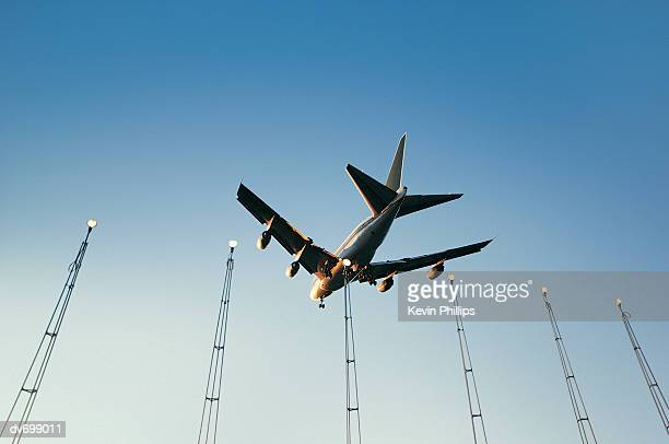 Low Angle View of Commercial Aircraft Flying Over Approach Lights, Heathrow Airport, UK