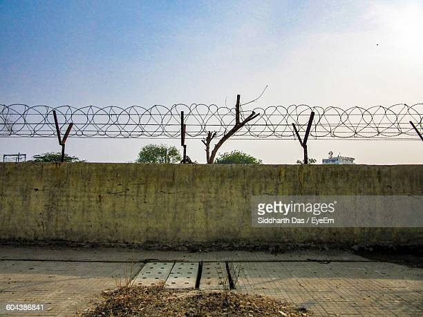 low angle view of concertina wire against clear sky - barbed wire stock pictures, royalty-free photos & images