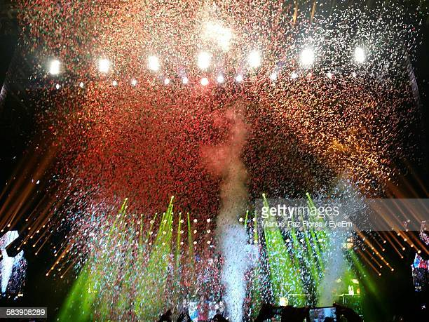 Low Angle View Of Confetti On Illuminated Stage At Concert