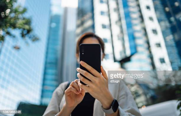 low angle view of confident and successful young asian businesswoman using smartphone in financial district, against corporate skyscrapers in the city. business on the go - cara oculta fotografías e imágenes de stock