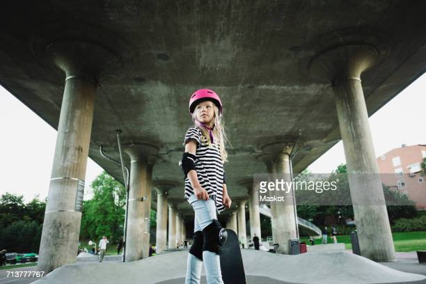 Low angle view of confident girl with skateboard standing at park