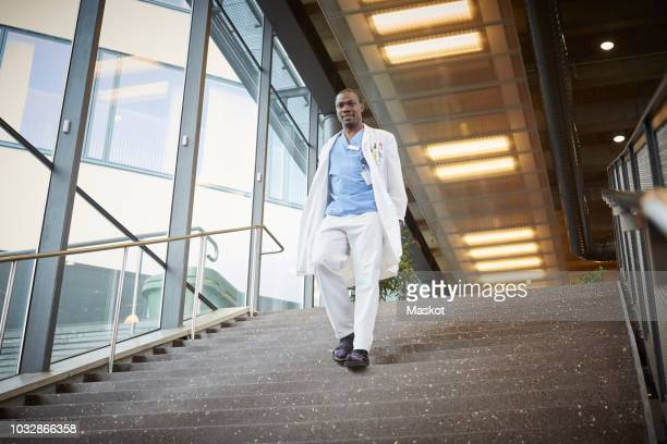 low angle view of confident male doctor moving down on staircase at hospital - down blouse photos et images de collection