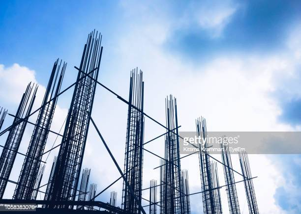 low angle view of construction site against cloudy sky - construction frame stock pictures, royalty-free photos & images