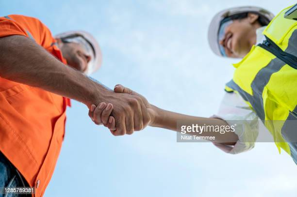 low angle view of construction site manager and engineer greeting each other. teamwork working together. - handshake stock pictures, royalty-free photos & images