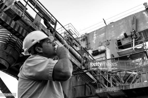 Low Angle View Of Construction Worker Smoking Cigarette While Looking At Factory