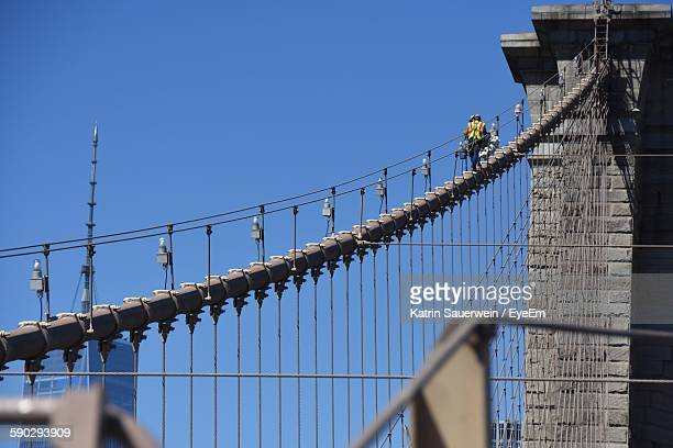 low angle view of construction workers on brooklyn bridge - brooklyn bridge stock pictures, royalty-free photos & images