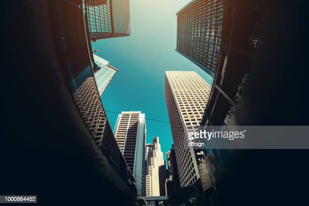 low angle view of contemporary corporate skyscrapers and busy city traffic in financial district of hong kong against blue sky - prosperity stock pictures, royalty-free photos & images
