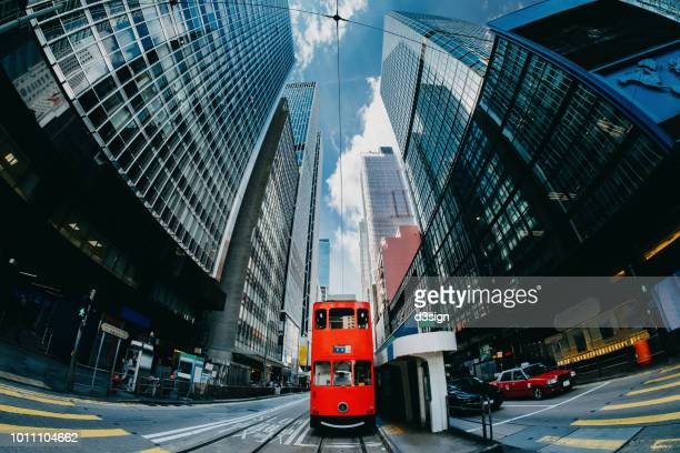 low angle view of contemporary corporate skyscrapers and red city tram in busy financial district of hong kong against blue sky - central stock pictures, royalty-free photos & images