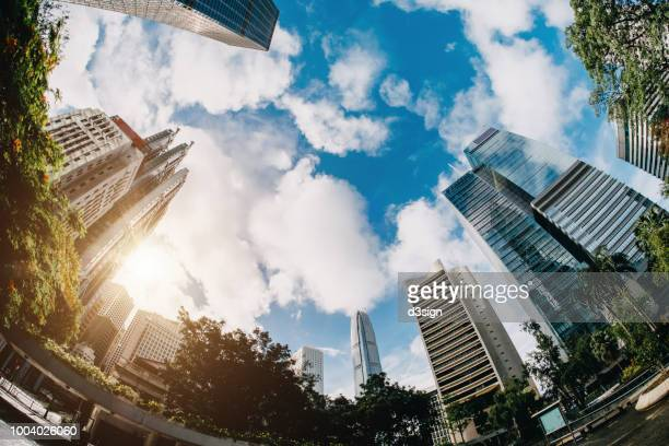 low angle view of contemporary corporate skyscrapers and urban park in financial district of hong kong on a fresh bright morning - 魚眼撮影 ストックフォトと画像