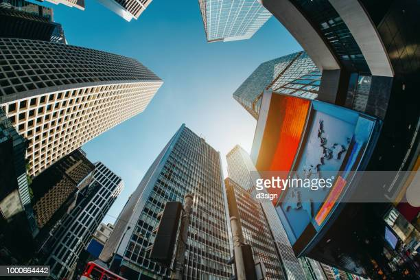 low angle view of contemporary corporate skyscrapers with urban architectural design in busy financial district of hong kong - nasdaq stock pictures, royalty-free photos & images