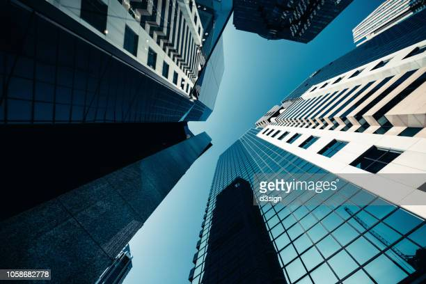 low angle view of contemporary corporate skyscrapers with urban architectural design in financial district of hong kong - bank financial building stock pictures, royalty-free photos & images