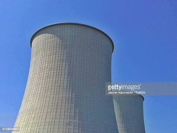 Low angle view of cooling towers against clear sky
