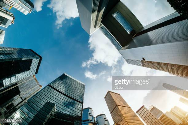 low angle view of corporate skyscrapers with contemporary architectural design in central business district against clear blue sky - finance and economy stock pictures, royalty-free photos & images