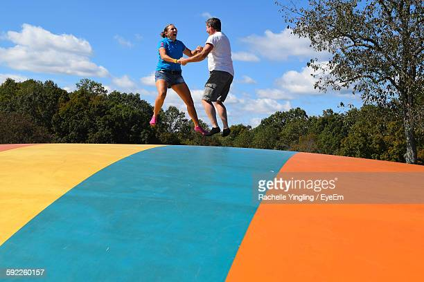 Low Angle View Of Couple Bouncing On Castle Against Sky