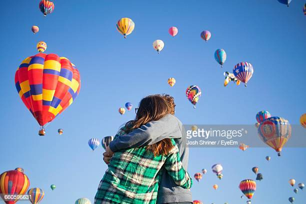 low angle view of couple embracing against hot air balloons flying in sky - oklahoma city stock pictures, royalty-free photos & images