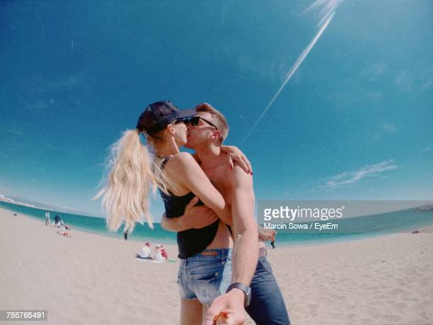 Low Angle View Of Couple Kissing At Beach Against Sky During Sunny Day