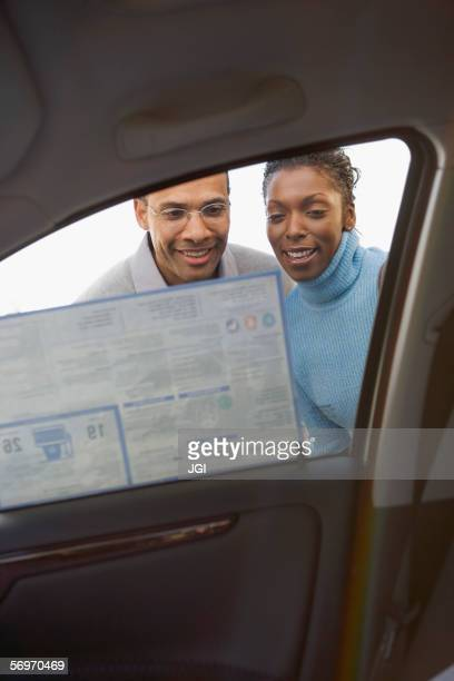 Low angle view of couple looking at sticker on new car window