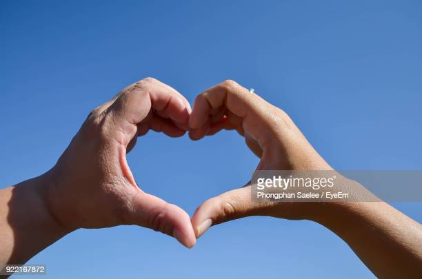 low angle view of couple making heart shape against clear blue sky - animal body part stock photos and pictures