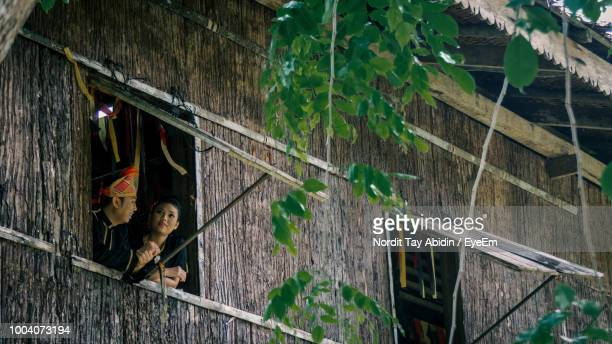 low angle view of couple talking wile standing by window - sarawak state stock pictures, royalty-free photos & images