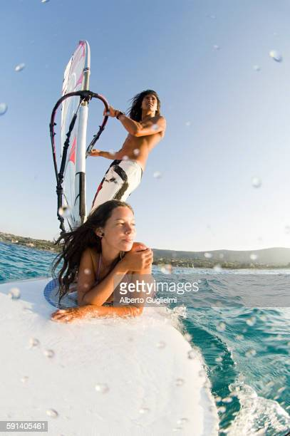 Low angle view of couple windsurfing on ocean