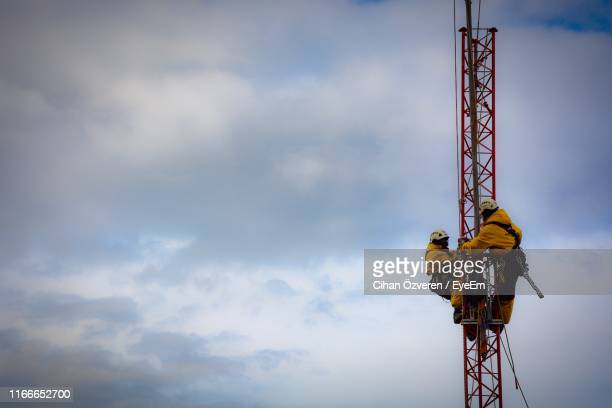 low angle view of coworker climbing built structure against cloudy sky - kran stock-fotos und bilder