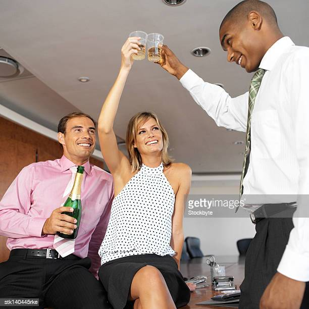 low angle view of co-workers toasting champagne in the office