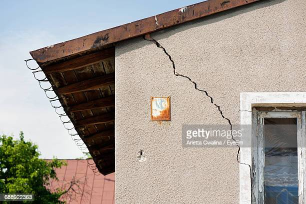 low angle view of cracked wall of house - ひびが入った ストックフォトと画像