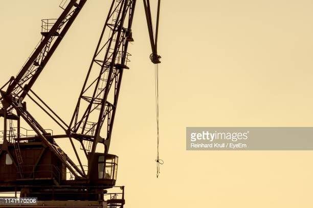 low angle view of crane against clear sky during sunset - baumaschine stock-fotos und bilder