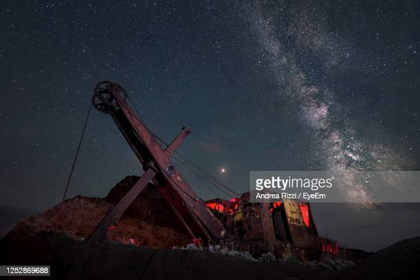 low angle view of crane against sky at night - andrea rizzi stockfoto's en -beelden