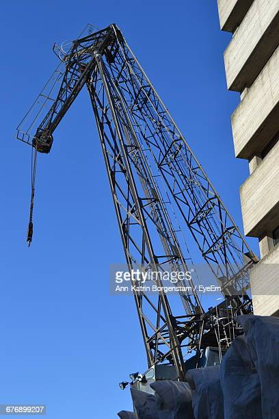 Low Angle View Of Crane At Construction Site Against Clear Blue Sky
