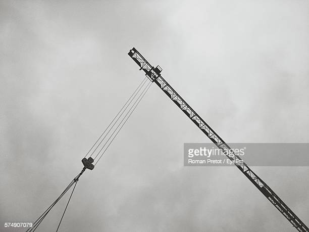 low angle view of crane at construction site against sky at dusk - roman pretot stock-fotos und bilder