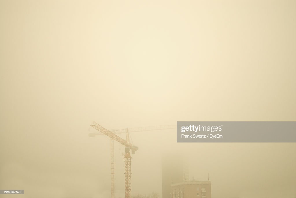 Low Angle View Of Crane By Building Against Sky During Foggy Weather : Stock-Foto