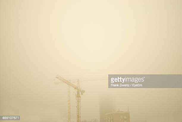 low angle view of crane by building against sky during foggy weather - frank swertz stockfoto's en -beelden