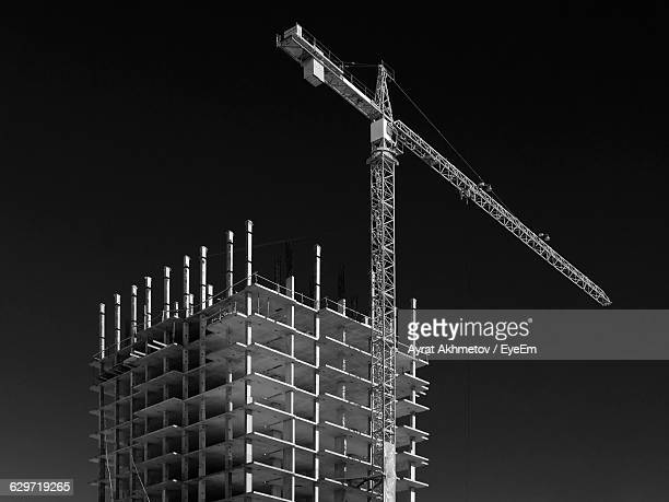 Low Angle View Of Crane By Incomplete Building Against Sky