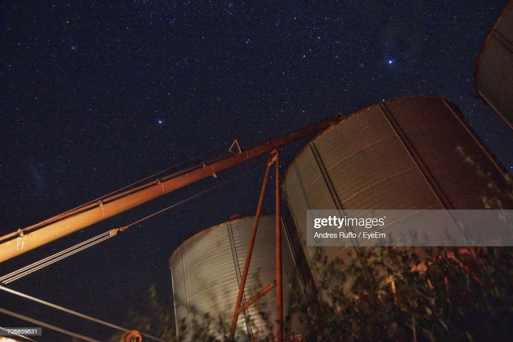 Low Angle View Of Crane By Silos Against Starry Sky At Night : Stock Photo