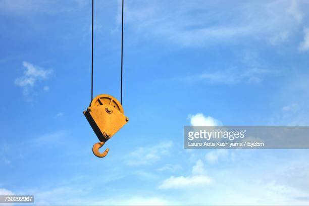 low angle view of crane hook against blue sky - crane stock pictures, royalty-free photos & images