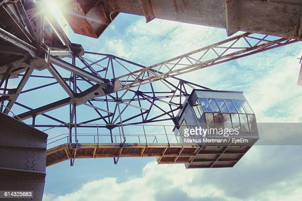 Low Angle View Of Crane Machinery At Open-Pit Coal Mine Against Sky