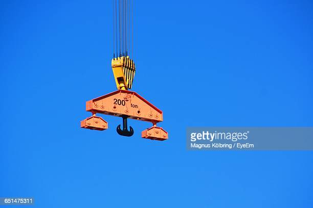 Low Angle View Of Crane Pulley Against Clear Blue Sky