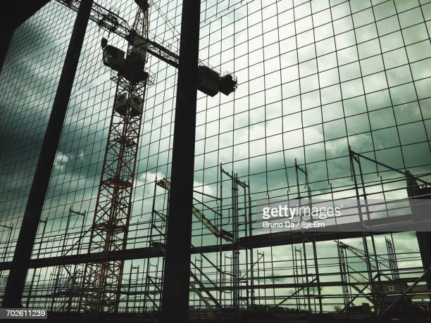 Low Angle View Of Crane Seen Through Fence Against Cloudy Sky