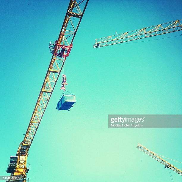 Low angle view of crane transporting container against clear blue sky