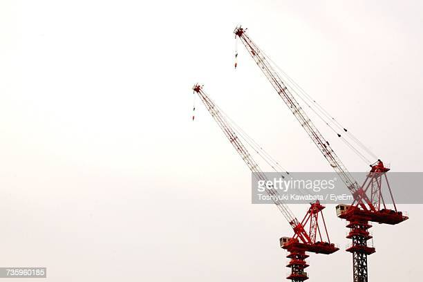 low angle view of cranes against clear sky - crane stock pictures, royalty-free photos & images