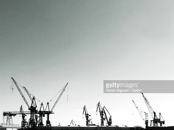 Low Angle View Of Cranes At Harbor Against Clear Sky