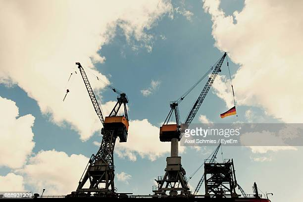 Low Angle View Of Cranes With German Flag At Commercial Dock Against Sky
