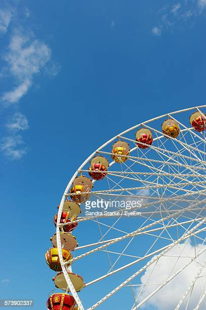 Low Angle View Of Cropped Ferris Wheel Against Blue Sky