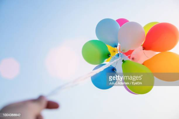 Low Angle View Of Cropped Hand Holding Colorful Helium Balloons Against Sky