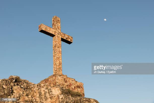 low angle view of cross against clear sky - crucifix stock pictures, royalty-free photos & images