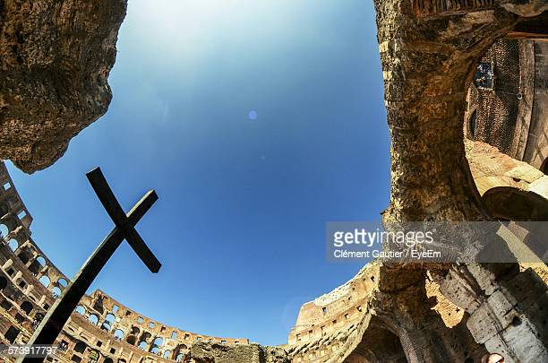 low angle view of cross at coliseum against sky - inside the roman colosseum stock photos and pictures