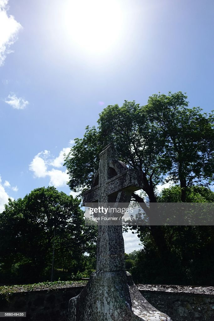 Low Angle View Of Cross In Cemetery And Trees Against Sky : Stock Photo