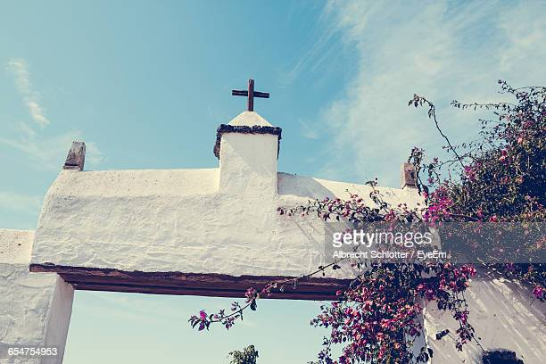low angle view of cross on entrance gate against sky - albrecht schlotter foto e immagini stock